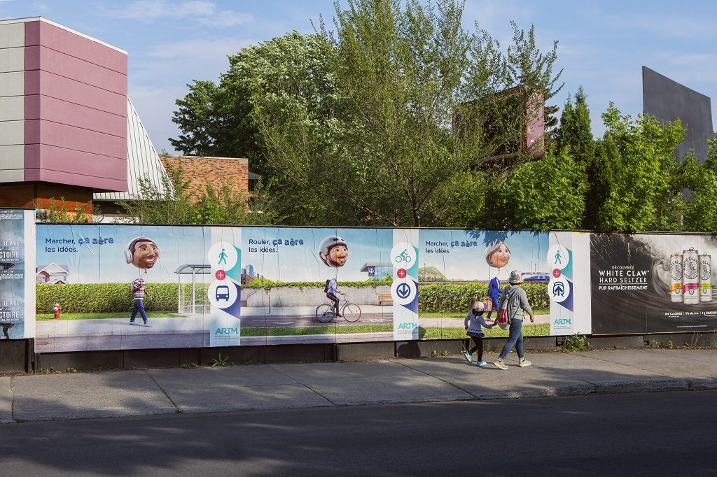 Affichage sauvage dans une rue de Montréal représentant les trois affiches de la campagne sur le transport actif.